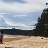 Bamboo Bungalow guests erect a volleyball net on the beach